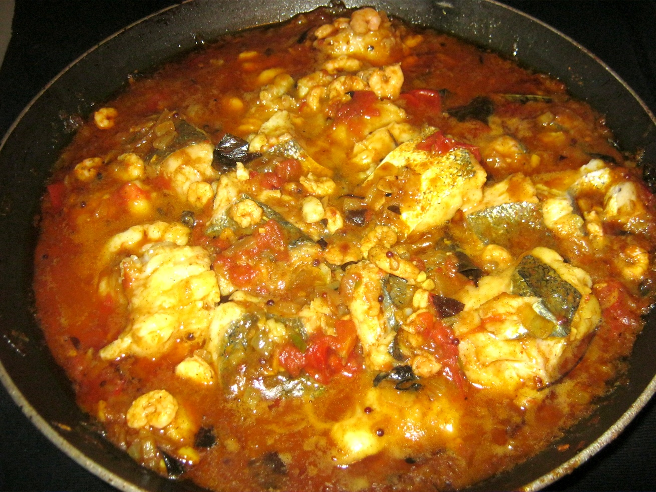 Hot Andhra Fish Curry with hake and prawns ready to be served