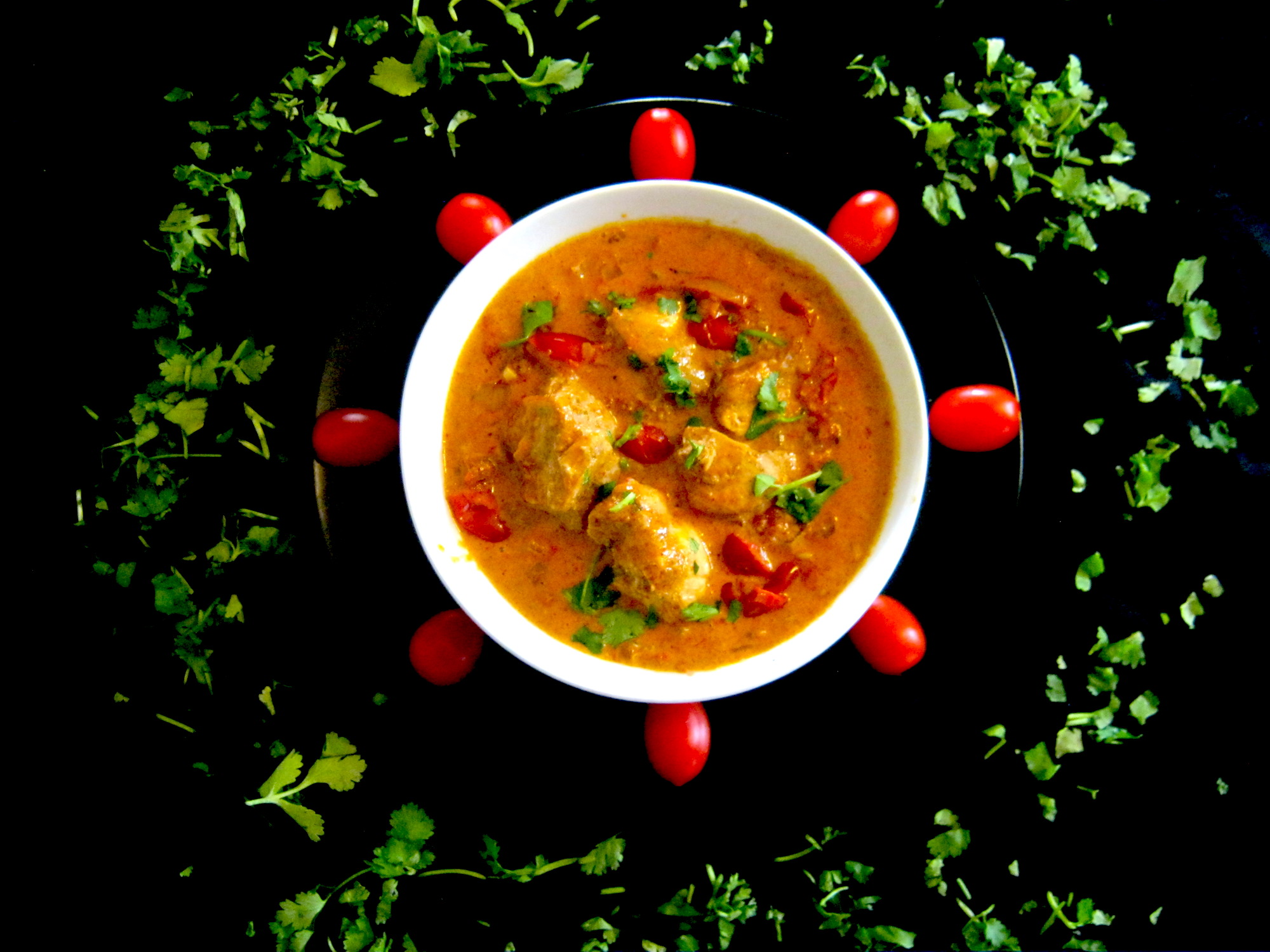 Butter chicken garnished with tomatoes and coriander leaves.