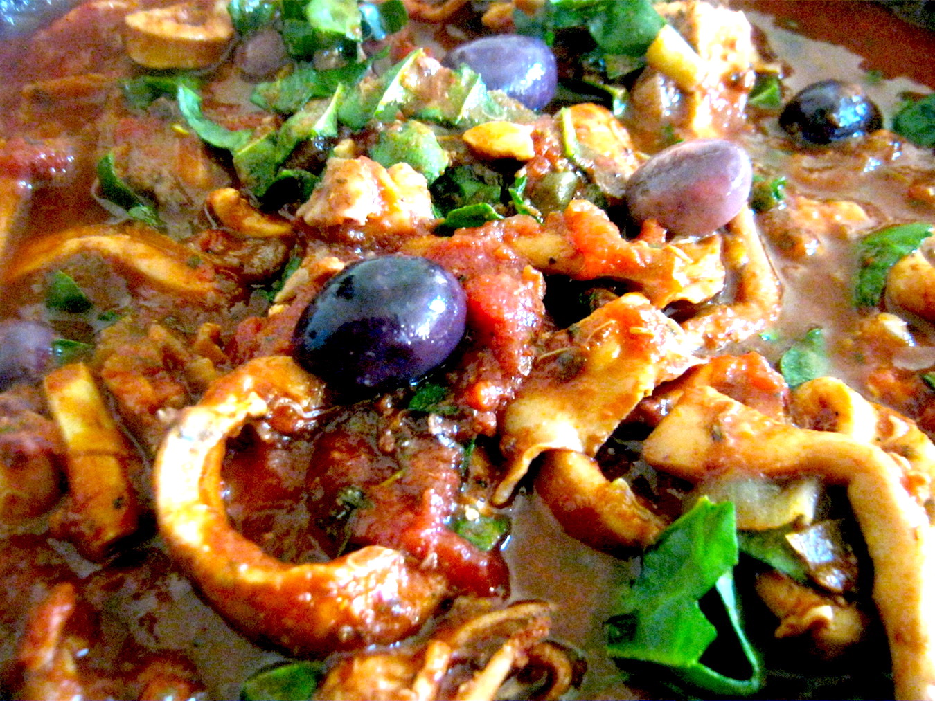 Calamari stew with olives and capers in a pan