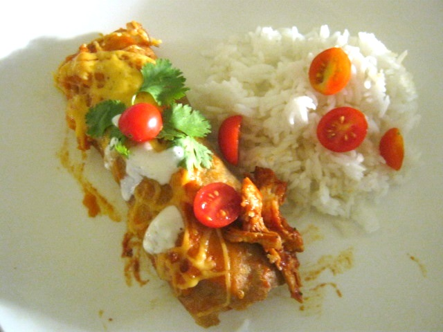 Chicken enchilada garnished with sour cream and fresh coriander on a plate.