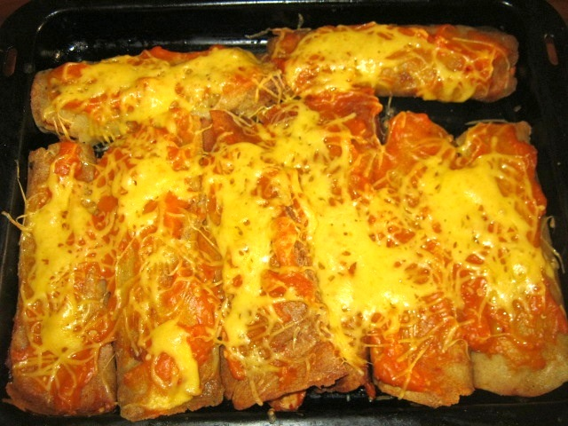 Chicken enchiladas baked in the oven and served with sour cream and fresh coriander.