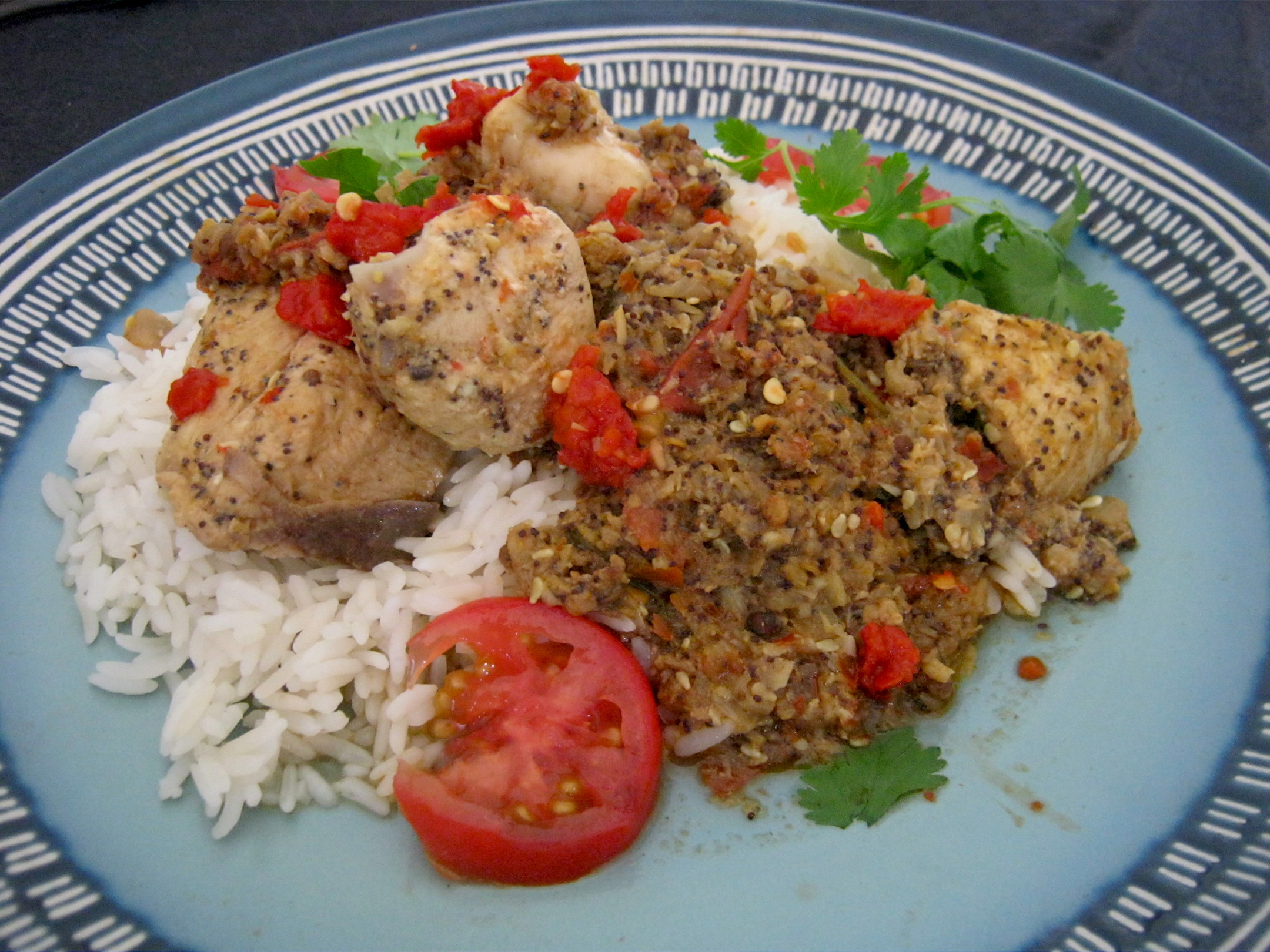 Kolhapuri chicken on a bed of steamed rice, garnished with tomato and fresh coriander leaves
