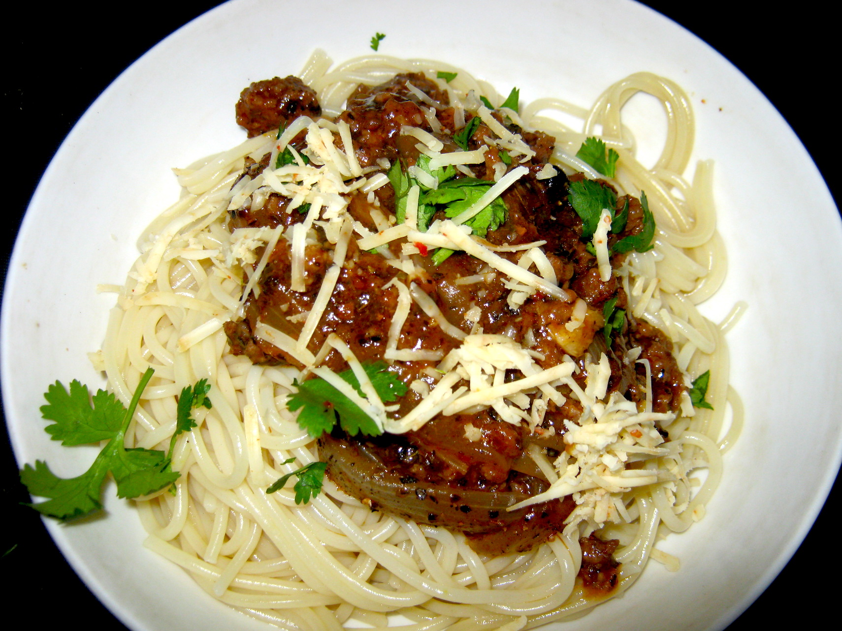 Spaghetti Bolognese garnished with freshly grated cheese and a few coriander leaves