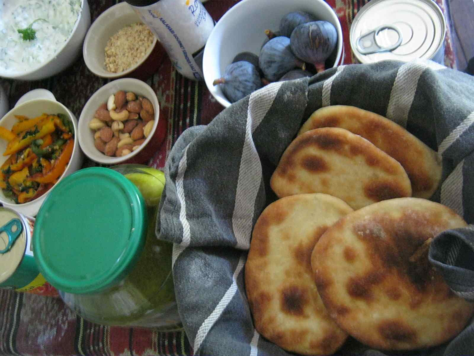 Fresh mini pita breads with condiments on a picnic blanket.