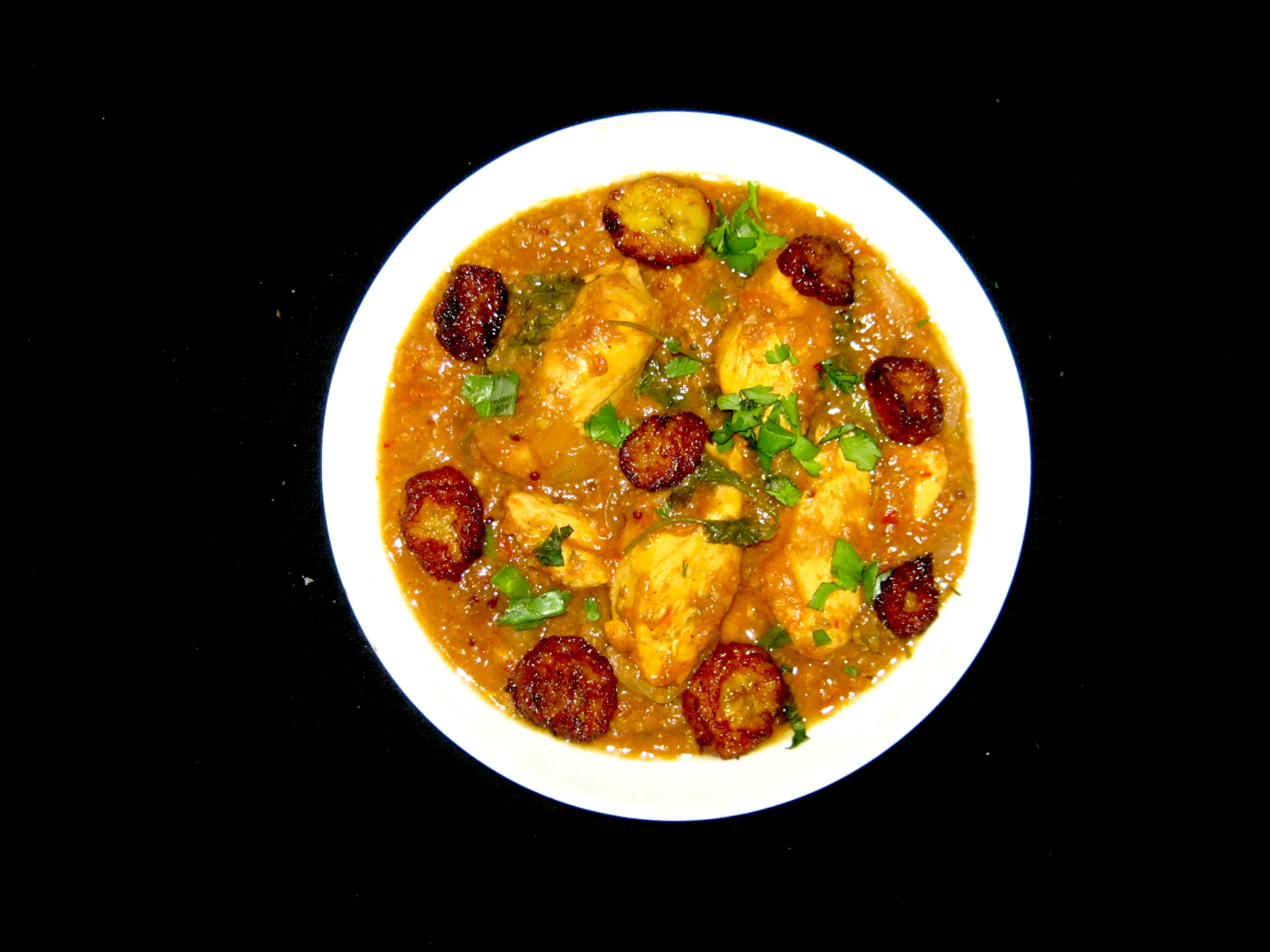 Green banana and chicken curry served in a white bowl garnished with coriander leaves and fried banana slices