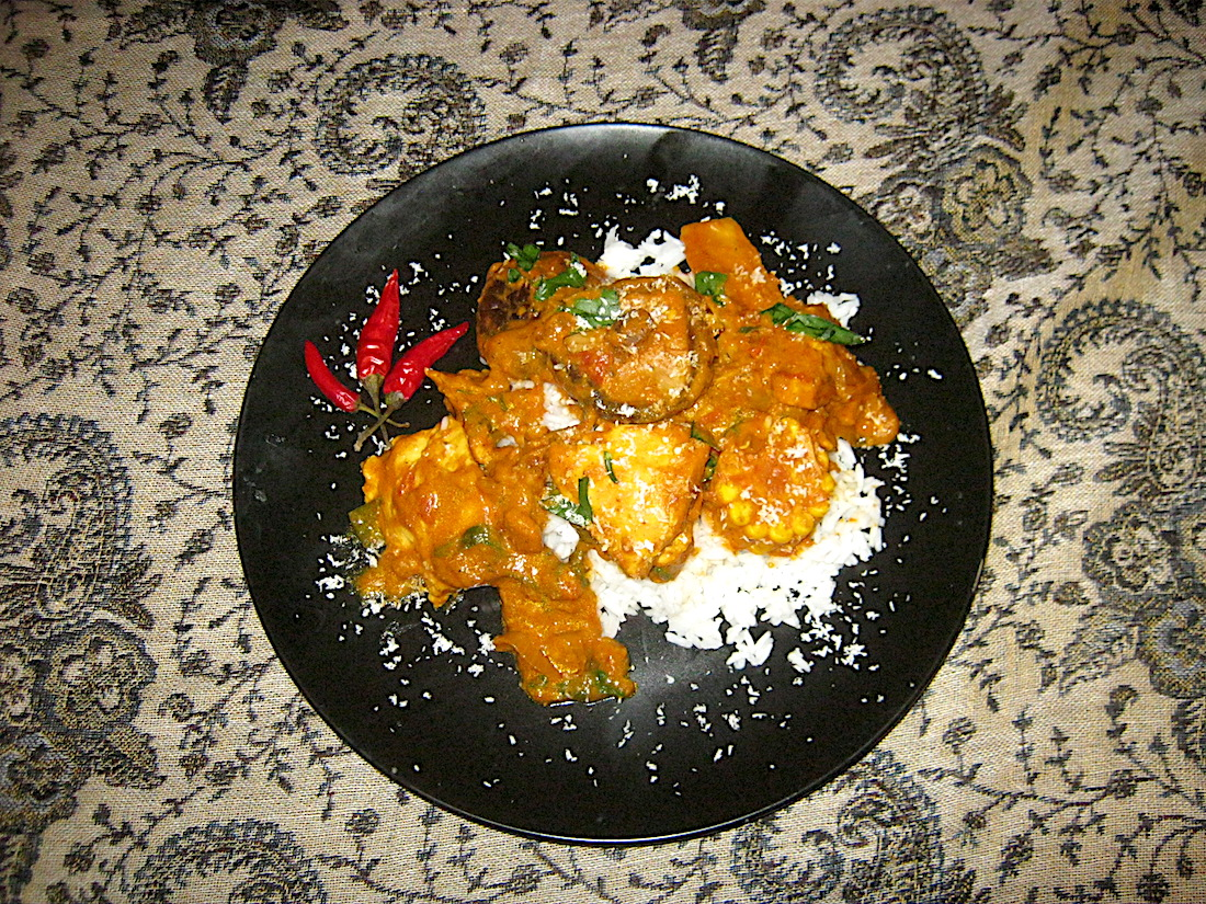 Cape town chicken curry garnished with desiccated coconut on a bed of rice