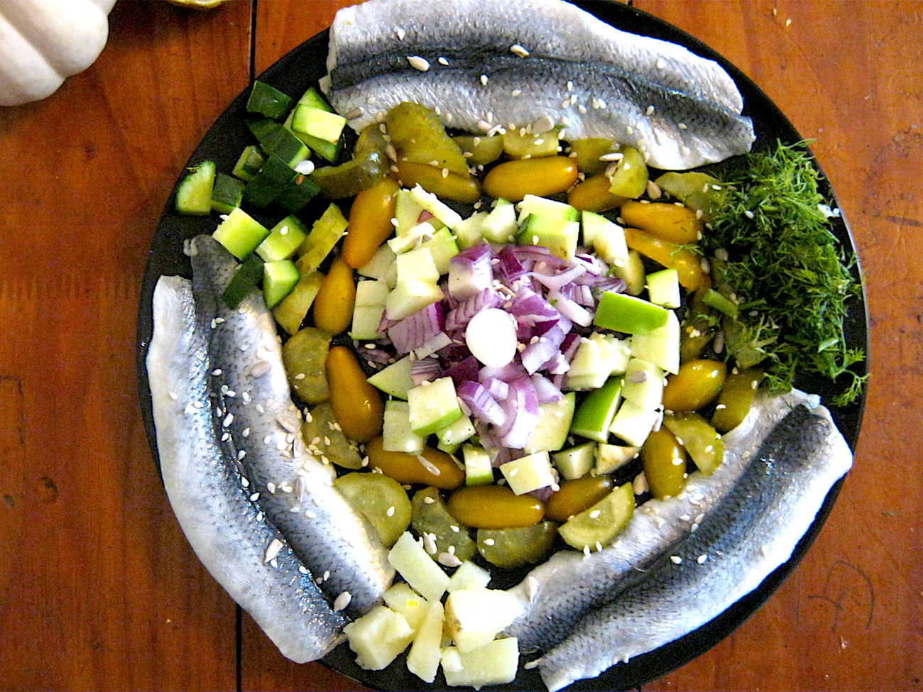 Pickled Bismarck Herring Salad with gherkins, capers, cucumbers, red onions, potatoes, apple juice and herbs. Follow our easy to follow step by step instructions and enjoy.