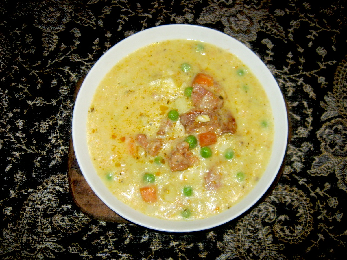 Potato leek soup  with smoked sausage and green garden peas served in a white bowl