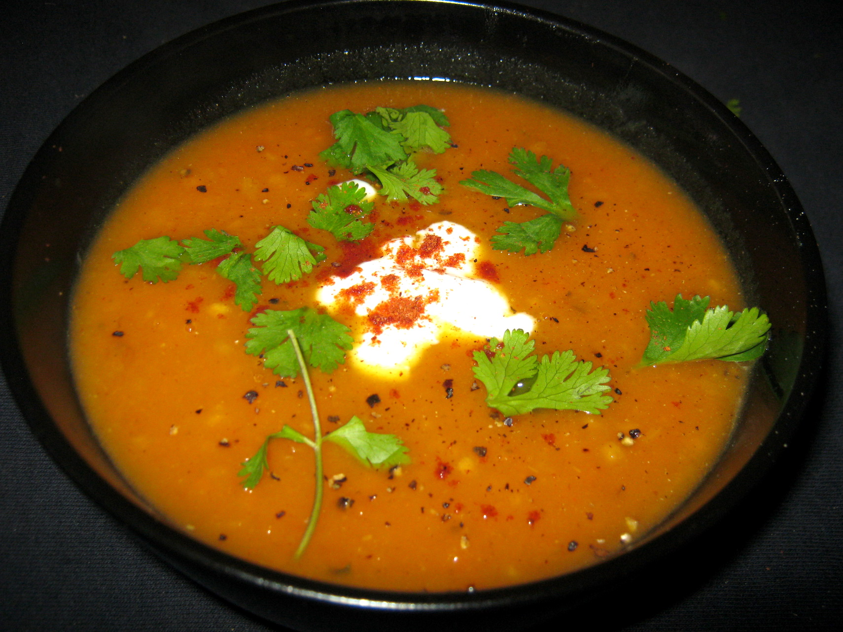 Sweet potato soup ala Alicia garnished with coriander leaves in a black bowl