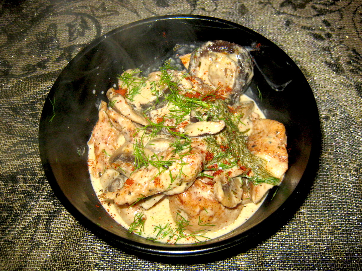 Chicken and mushroom sauce in a black bowl