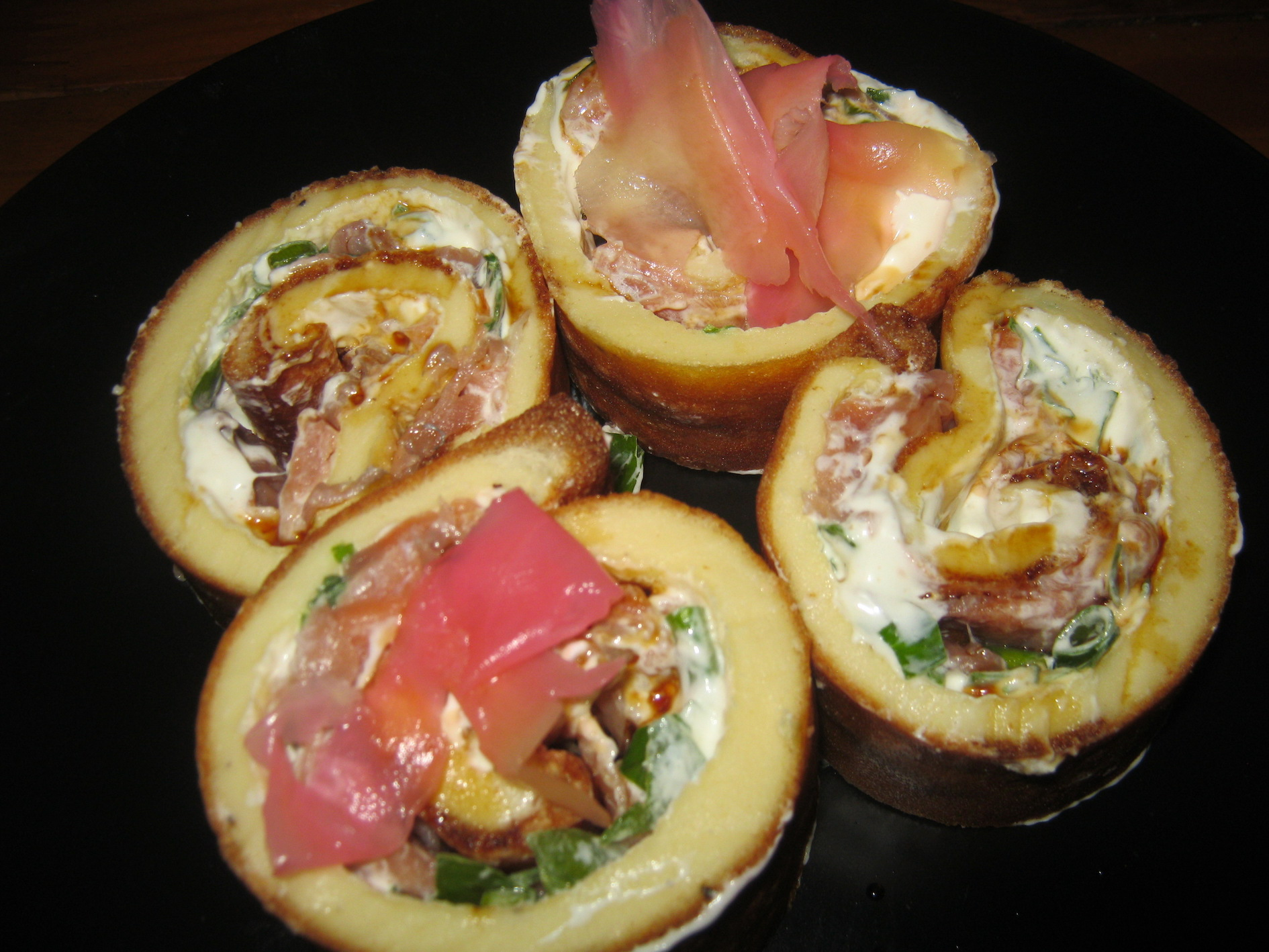 Pancake rolls with smoked salmon, sour cream, wasabi and spring onion filling, topped with soy sauce and pickled ginger
