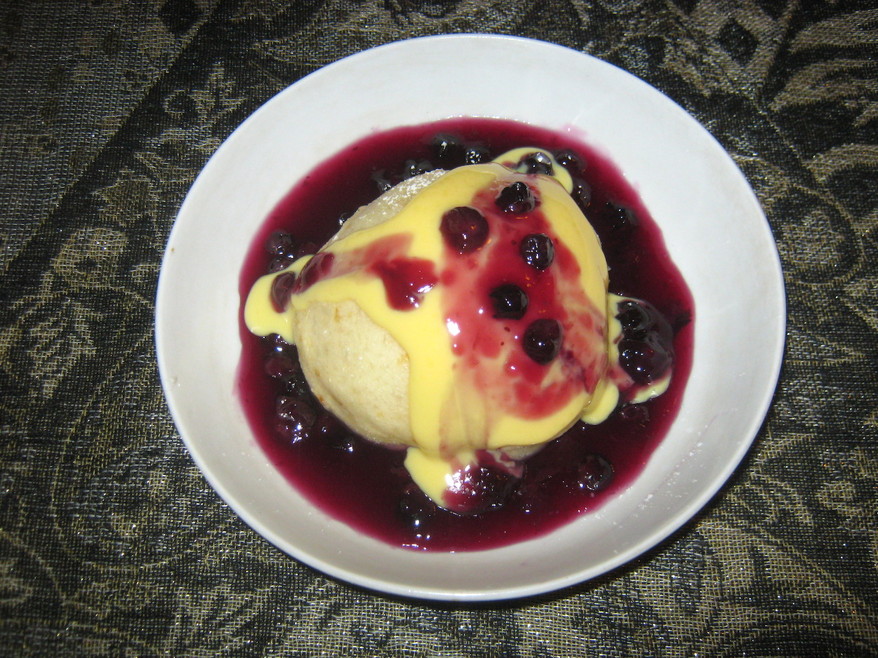 Blueberry sauce and custard on a yeast dumpling in a white bowl
