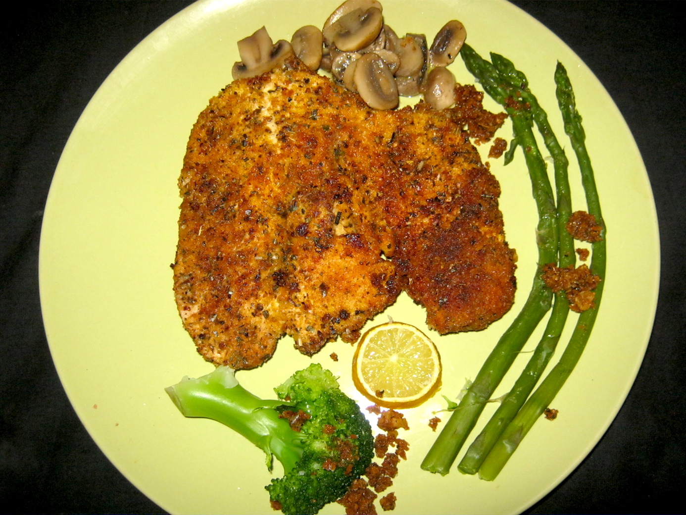 Chicken Schnitzel with green asparagus, button mushrooms, broccoli, buttered breadcrumbs and lemon slice