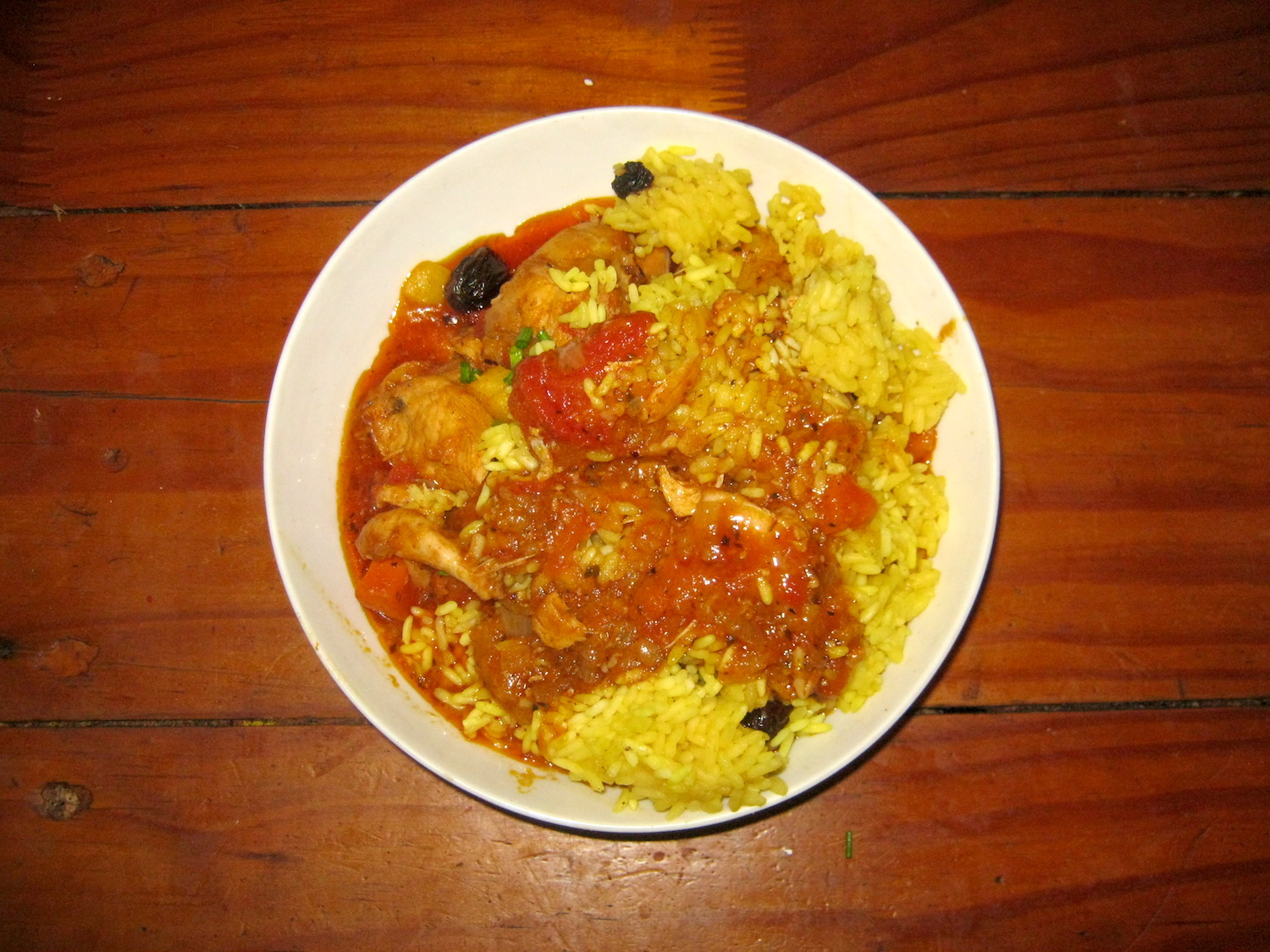 African chicken stew with turmeric rice in white bowl