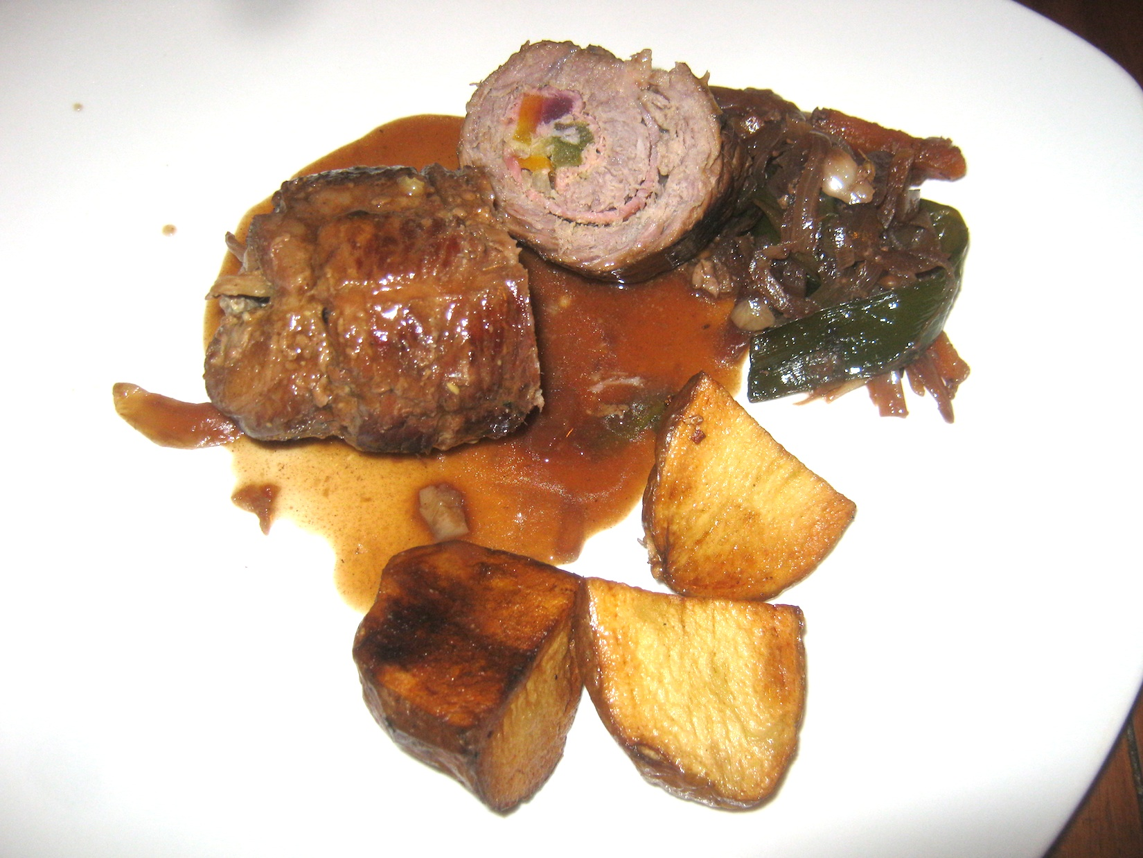 Beef Roulade (Rinderroulade) with deep fried potatoes, gravy and braised vegetables