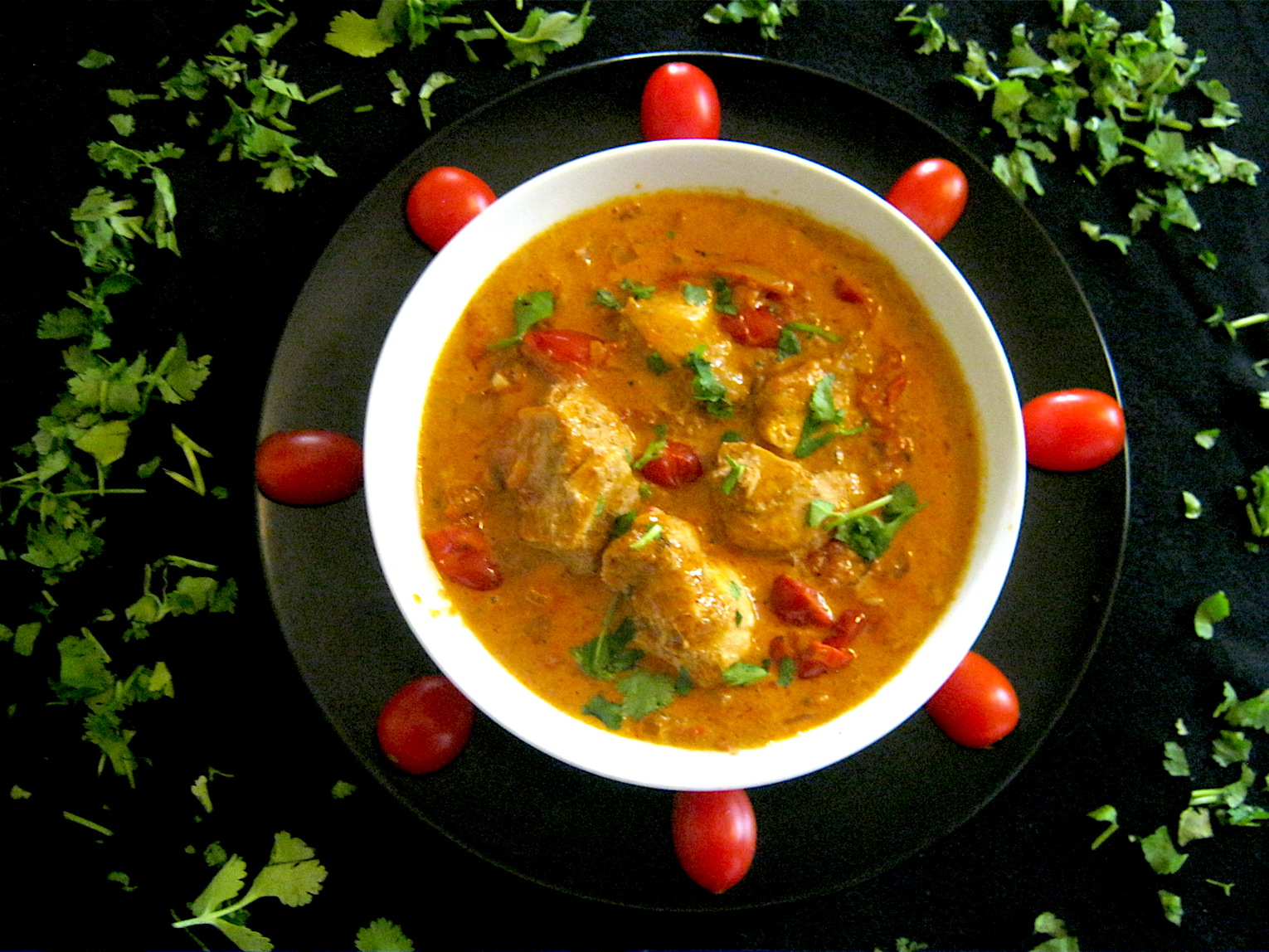 Butter Chicken garnished with tomatoes and coriander leaves