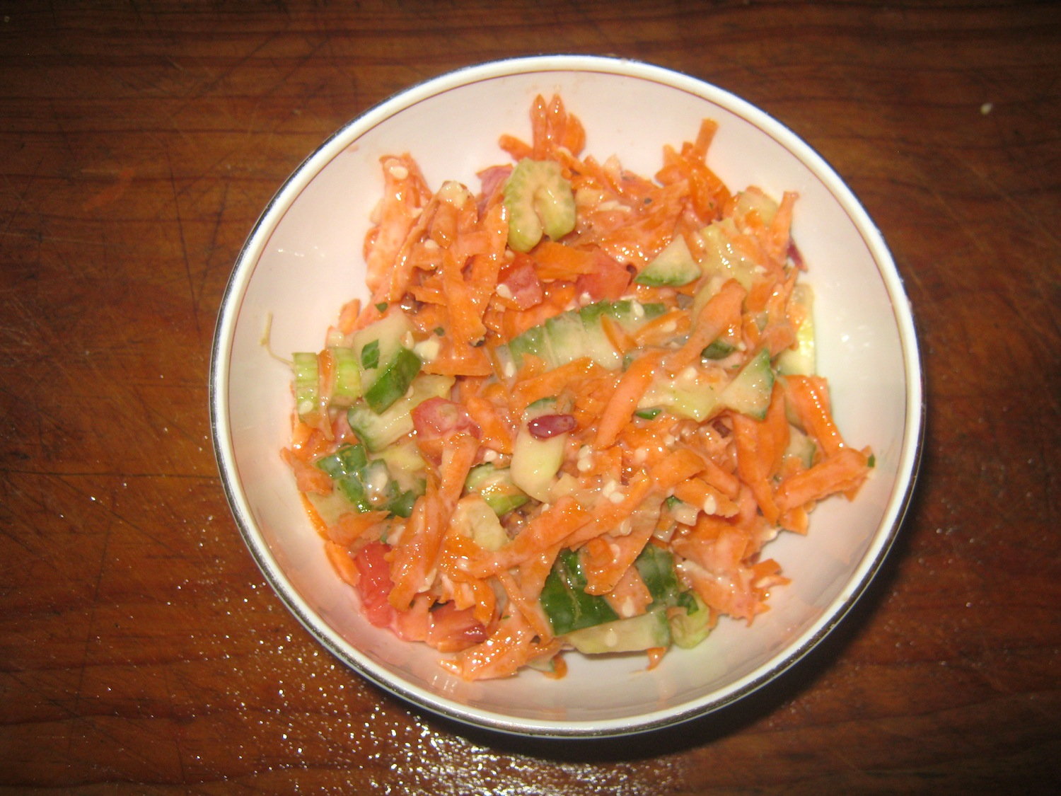 Carrot salad with chili and yogurt mint sauce in white bowl