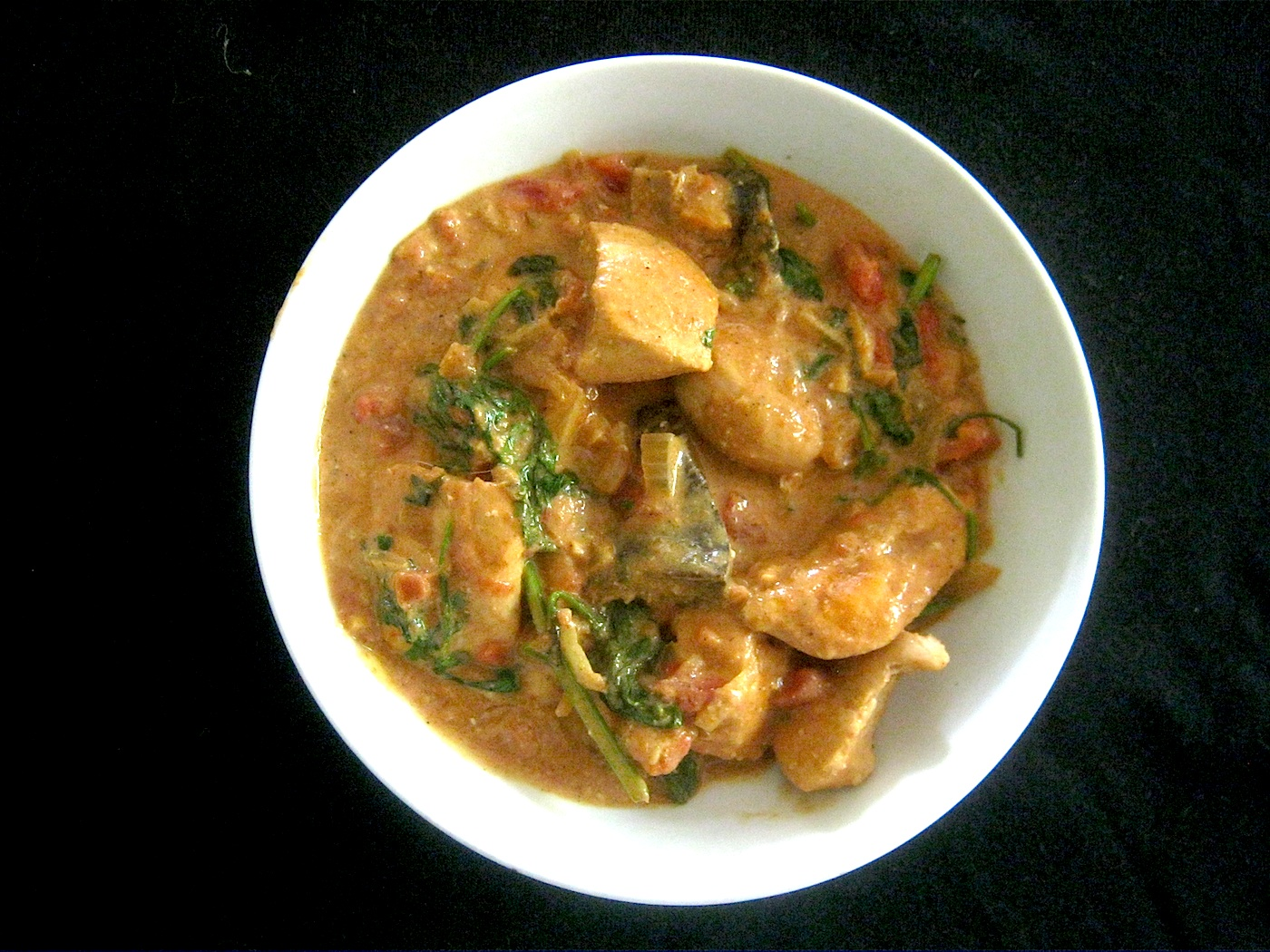 Indian chicken curry with mushrooms and coriander in a white bowl