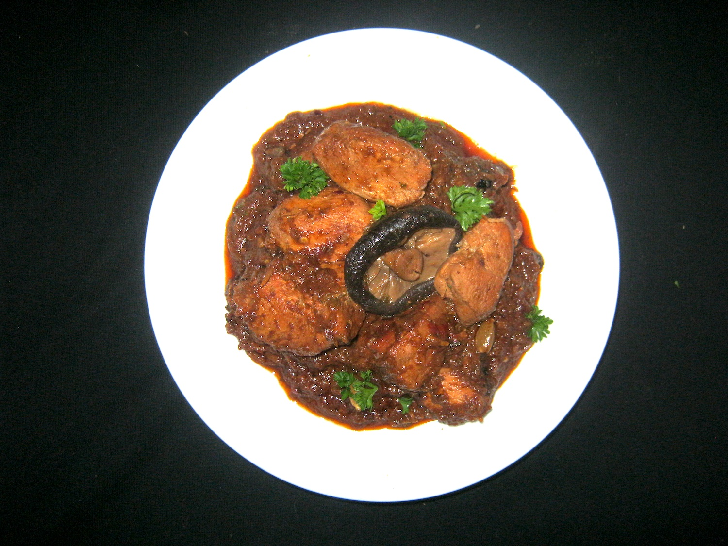 Chicken Rogan Josh with shiitake mushrooms served in a white bowl