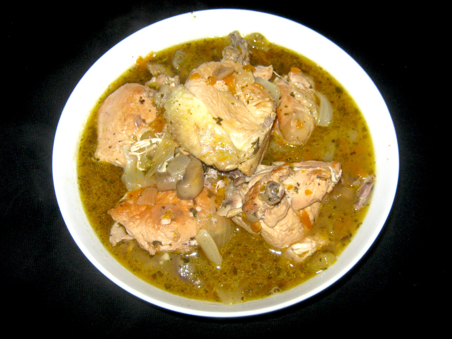 Coq au vin blanc (Chicken in white wine sauce) served in a white bowl