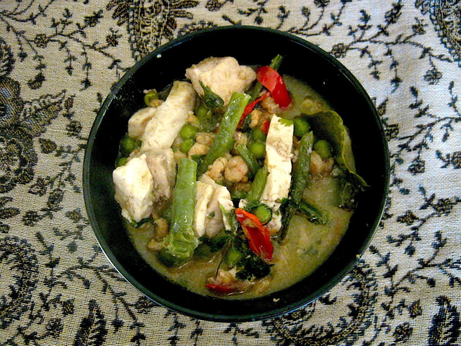 Thai green curry with swordfish and prawns in a black bowl
