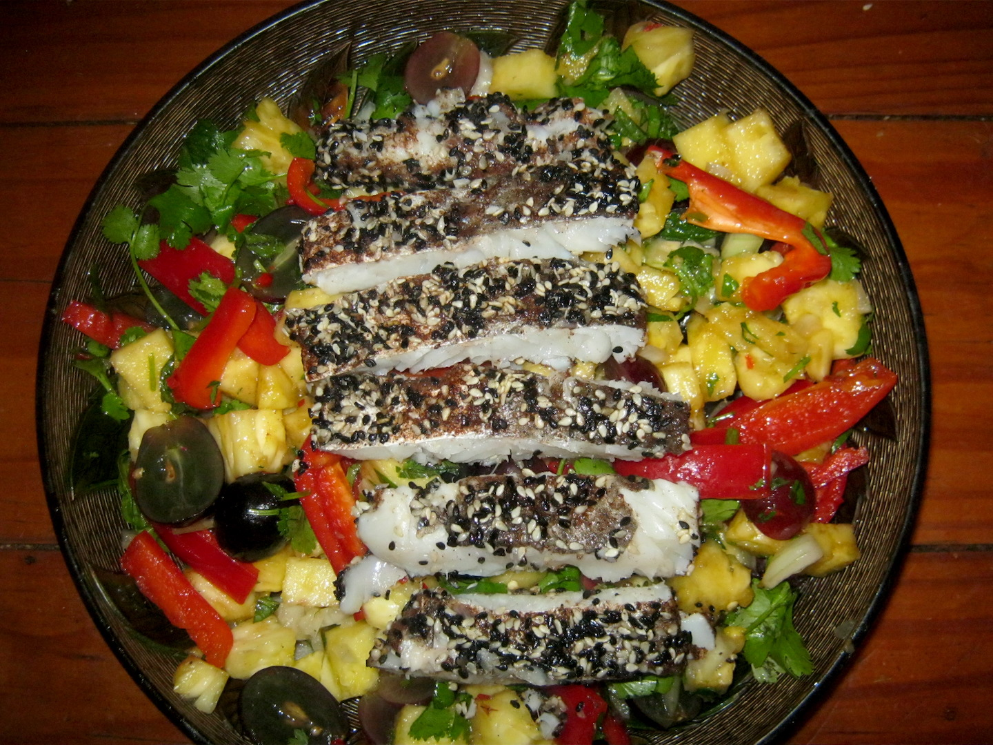 Hake in Cinnamon Sesame Crust on a bed of pinapple grape and pepper salad