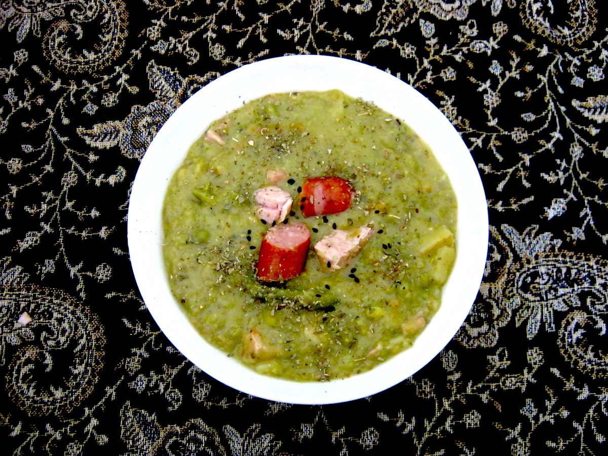 Hearty Pea Soup with Kassler chops and Smoked Sausage in a white bowl
