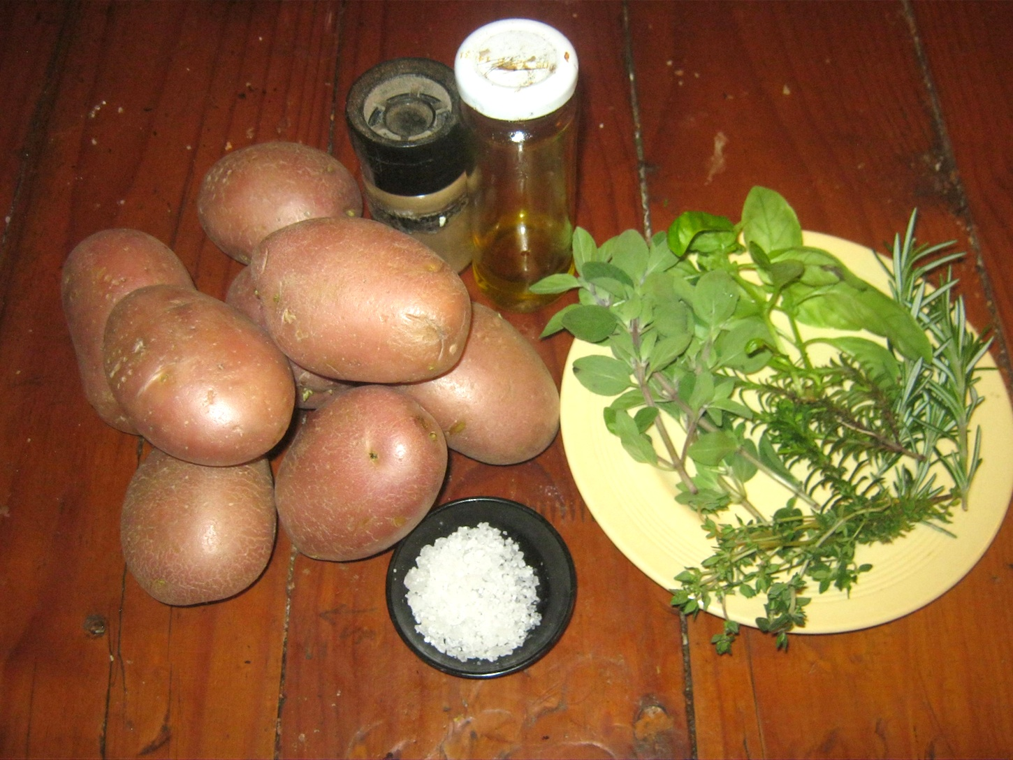 Ingredients for baked potatoes with fresh garden herbs.