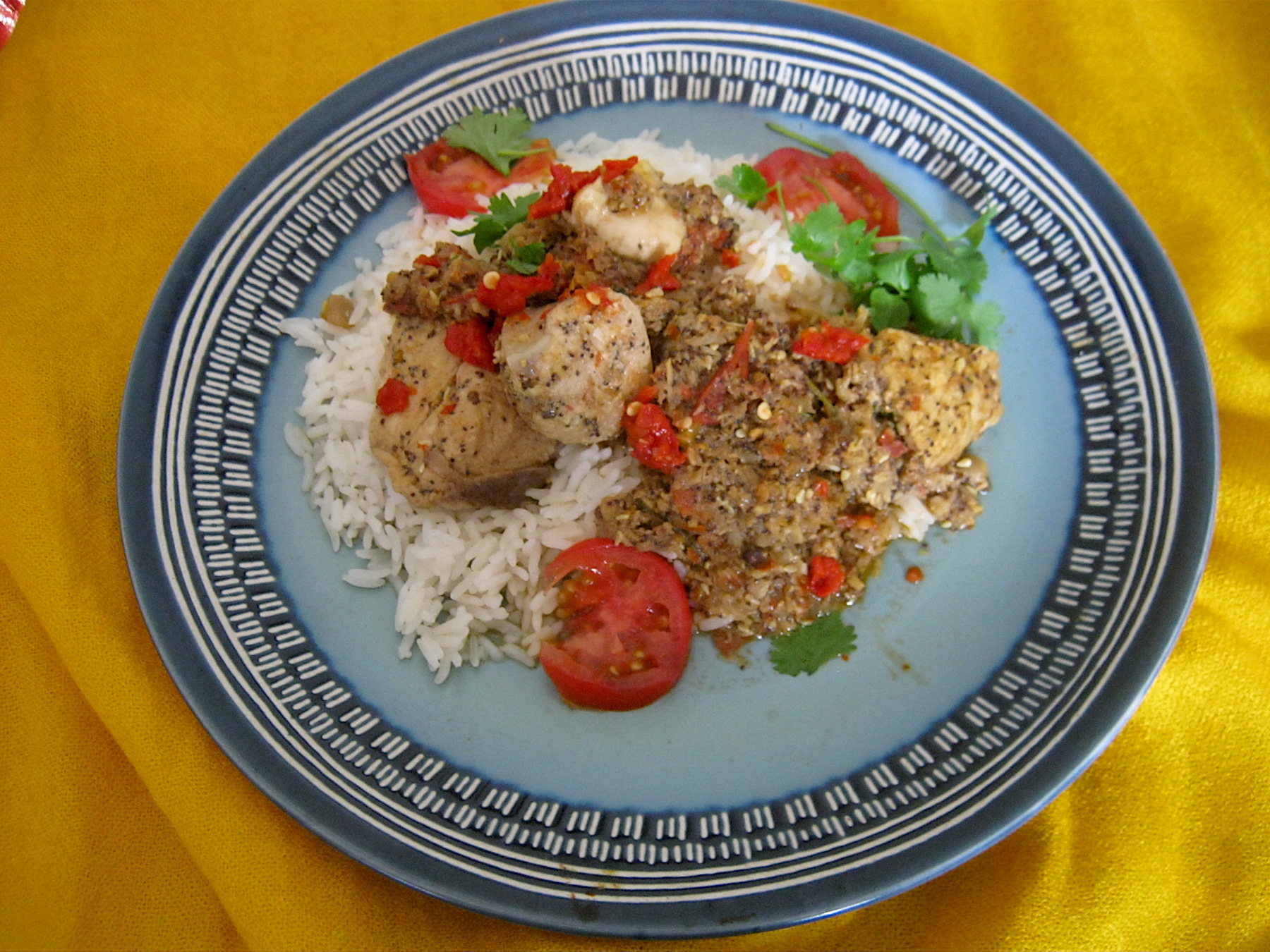 Kolhapuri chicken with steamed rice, garnished with tomato slices and fresh coriander leaves