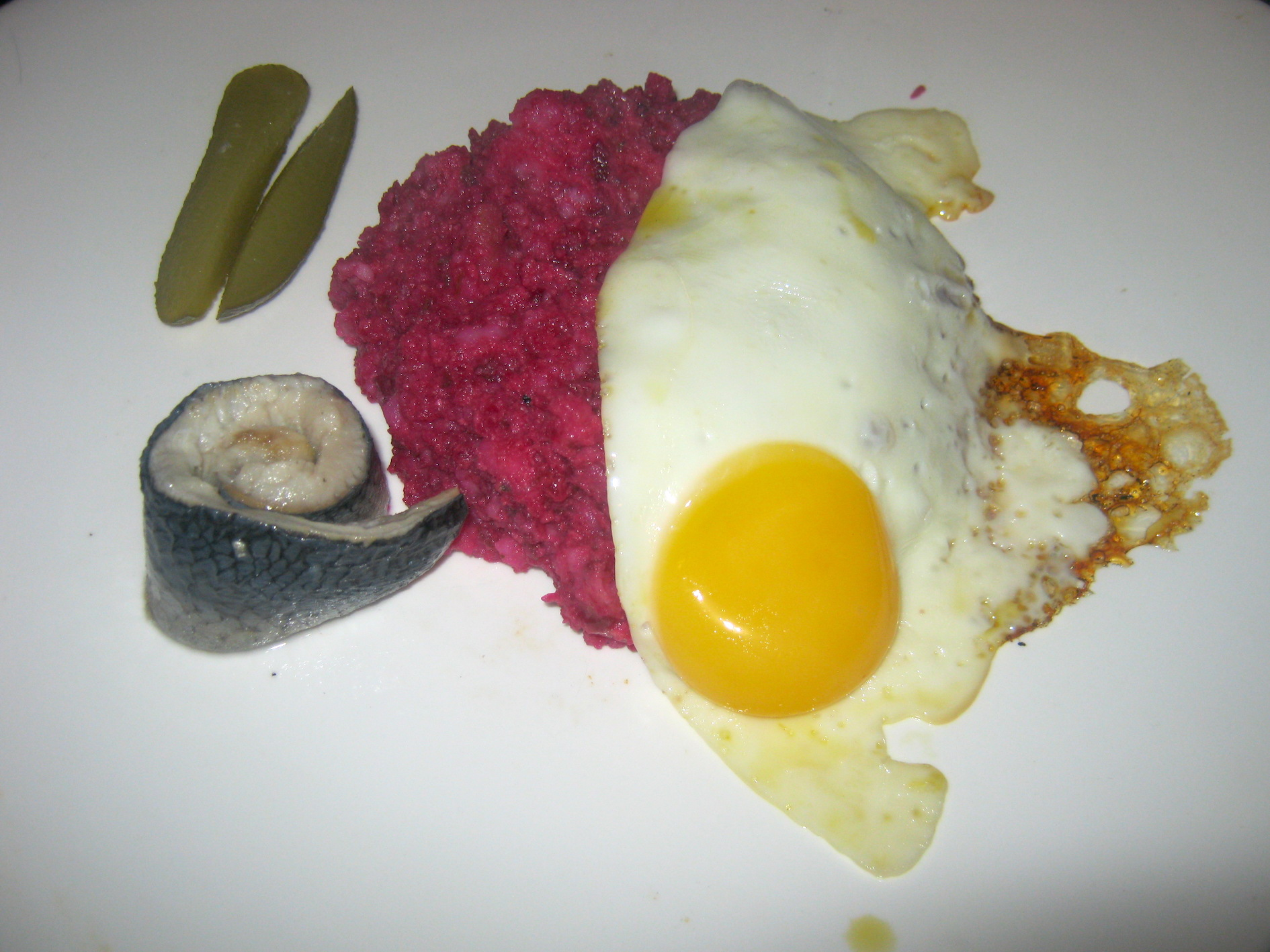 Hamburger Labskaus is a traditional North German dish with gherkins, beetroot, potatoes, eggs and pickled herring