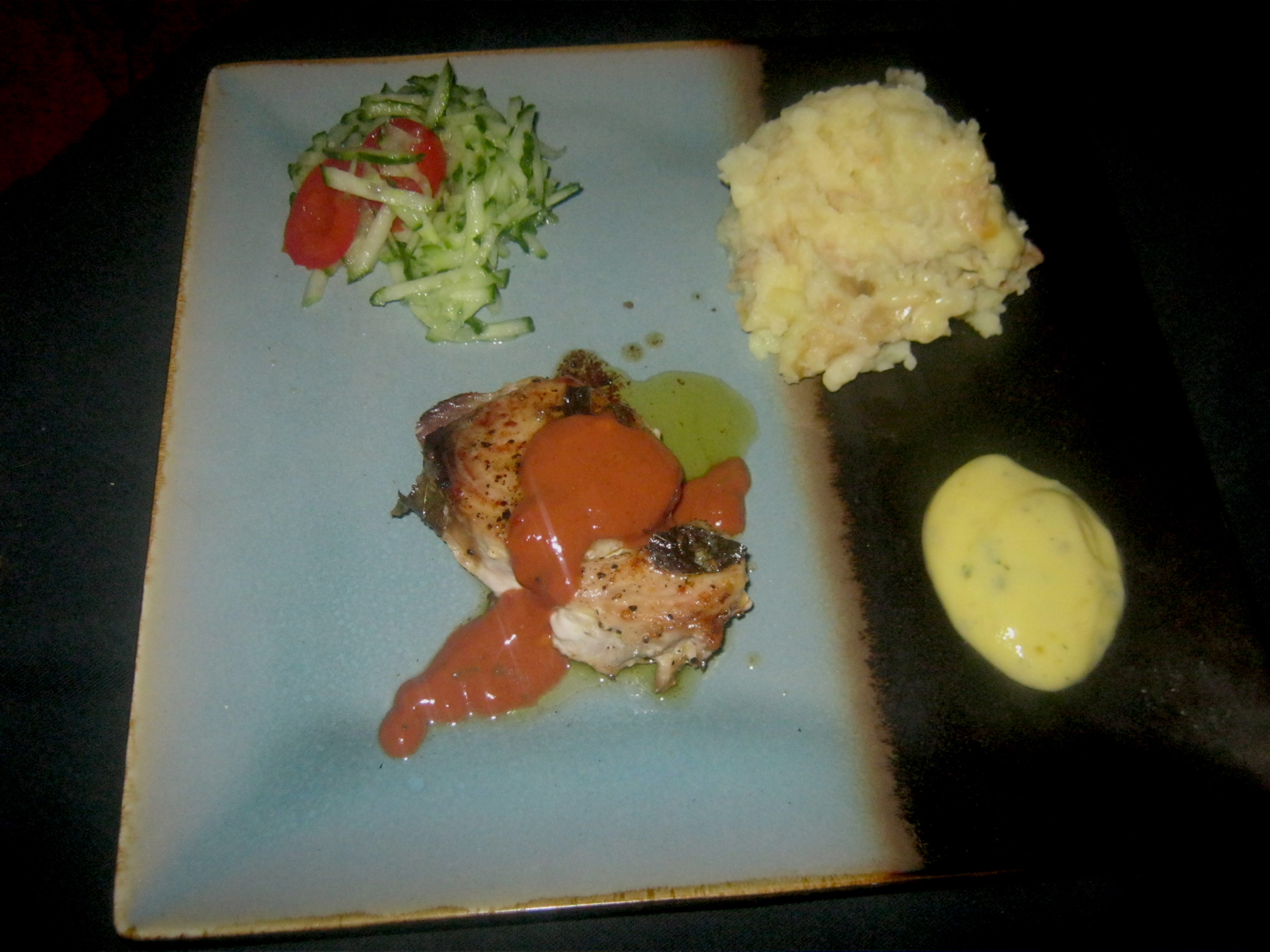 Pan fried marlin steak with mashed potato, homemade herb mayonaise, sauce andalouse and tomato and cucumber salad
