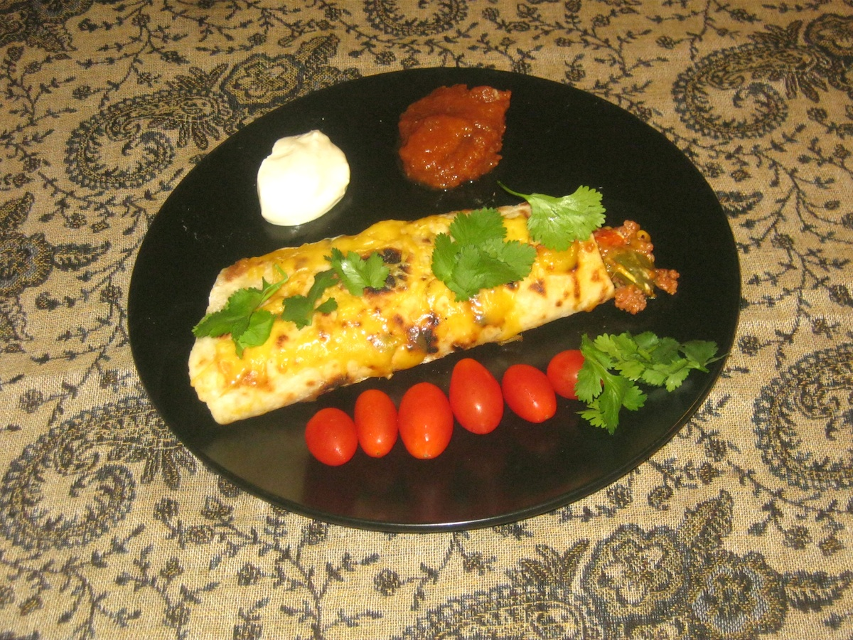 Mexican Beef Burrito with tomatoes, coriander, sour cream and tomato chutney