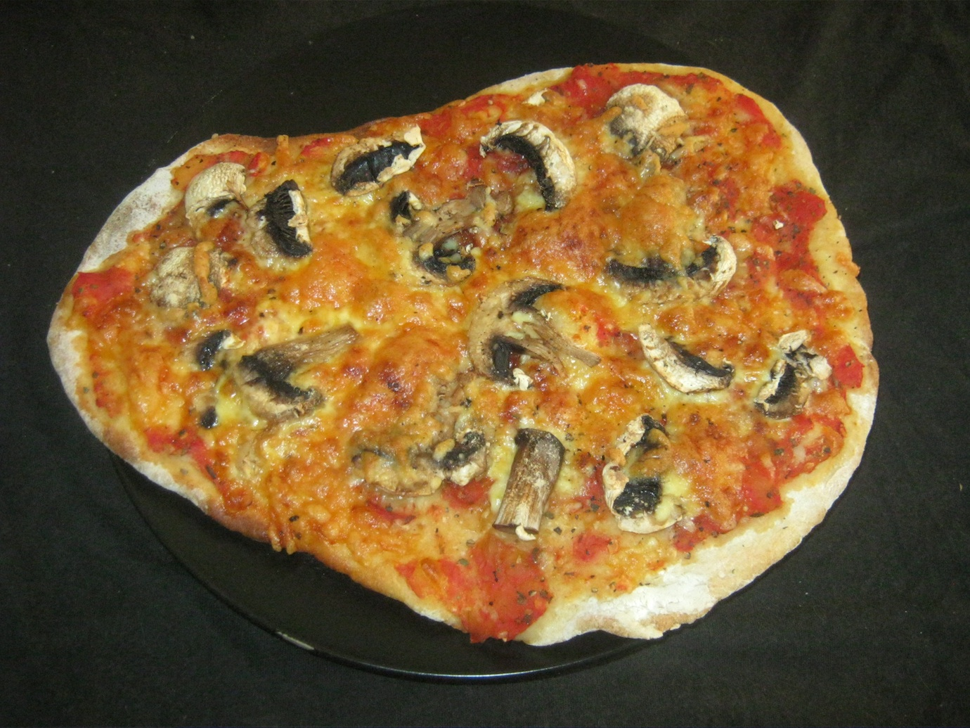 Pizza Funghi served on a black plate