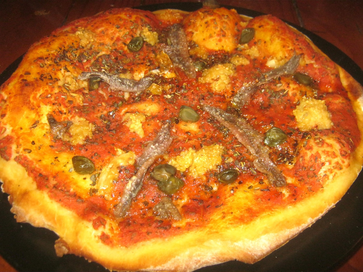 A freshly baked Pizza Marinara served on a black plate