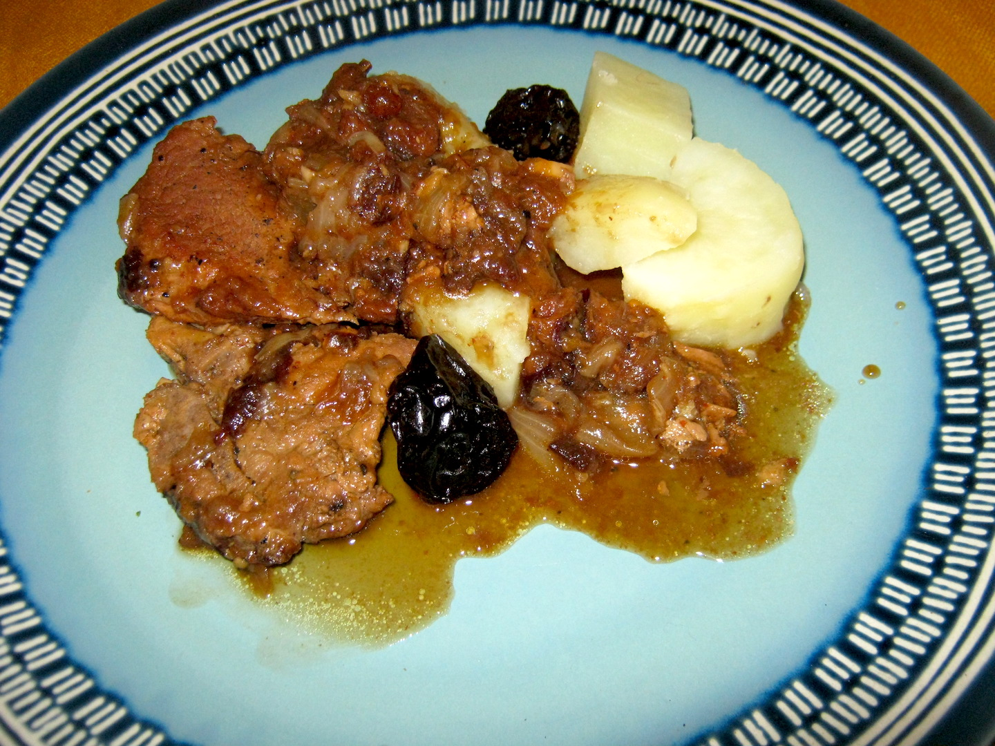 Pork neck chops in prune sauce on a plate