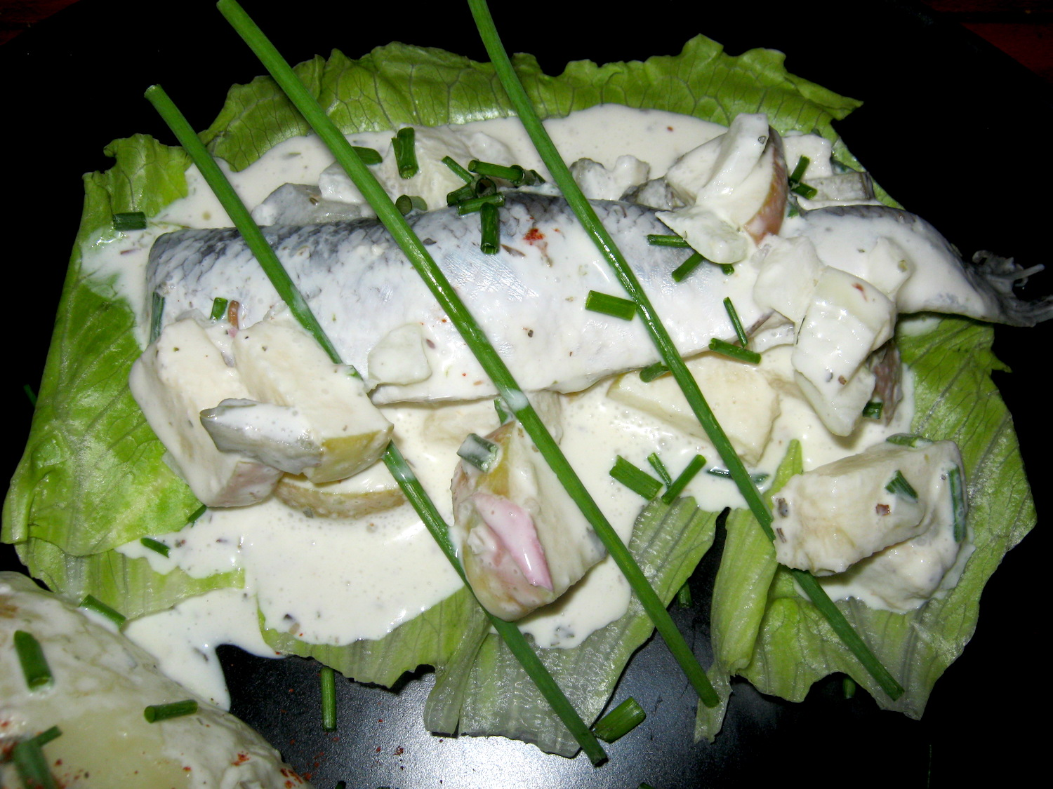 Herring fillet in sweet and sour marinade on a lettuce leaf