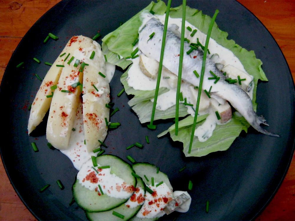 Pickled Herring fillets (Sahnehering) in sweet and sour cream and yoghurt marinade with peeled jacket potatoes and cucumber on a black plate
