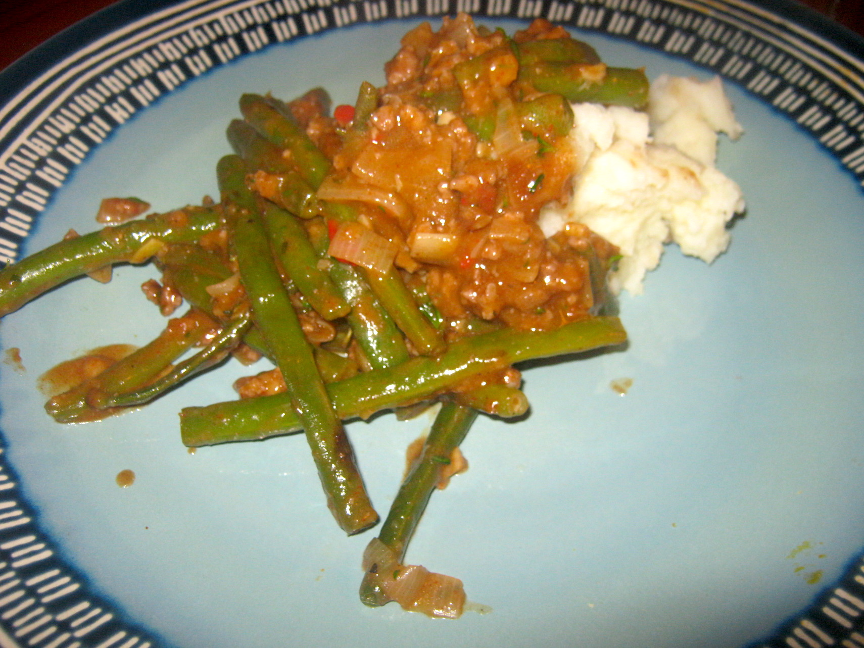 Green bean and mince stew on a plate served with mashed potatoes on a plate