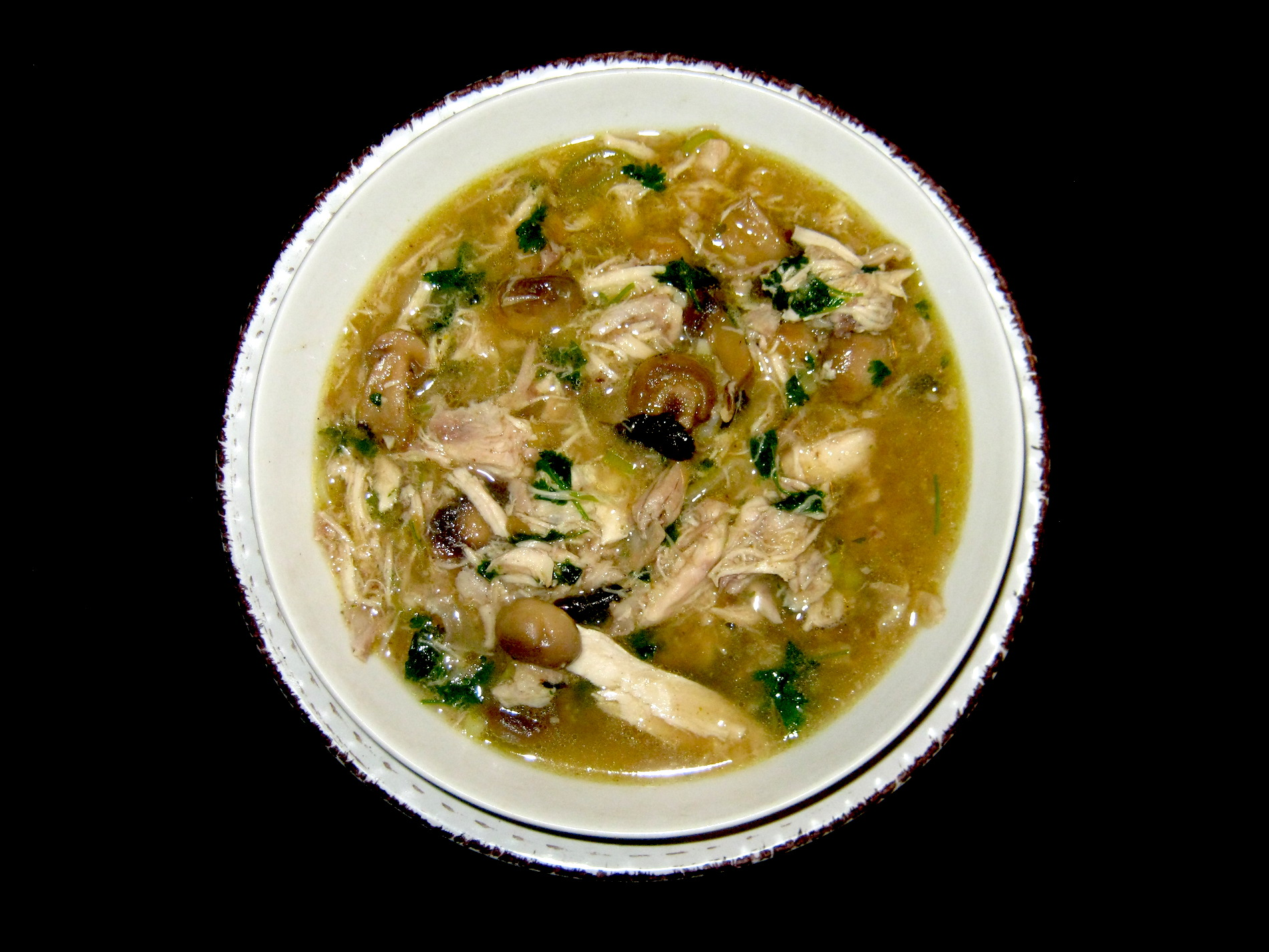 Thai chicken and mushroom soup in a white bowl