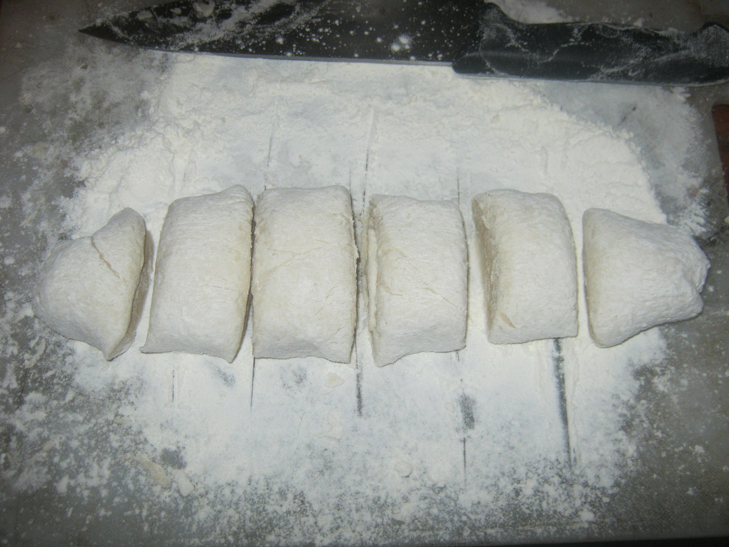 Dough divided into 6 pieces on a large board