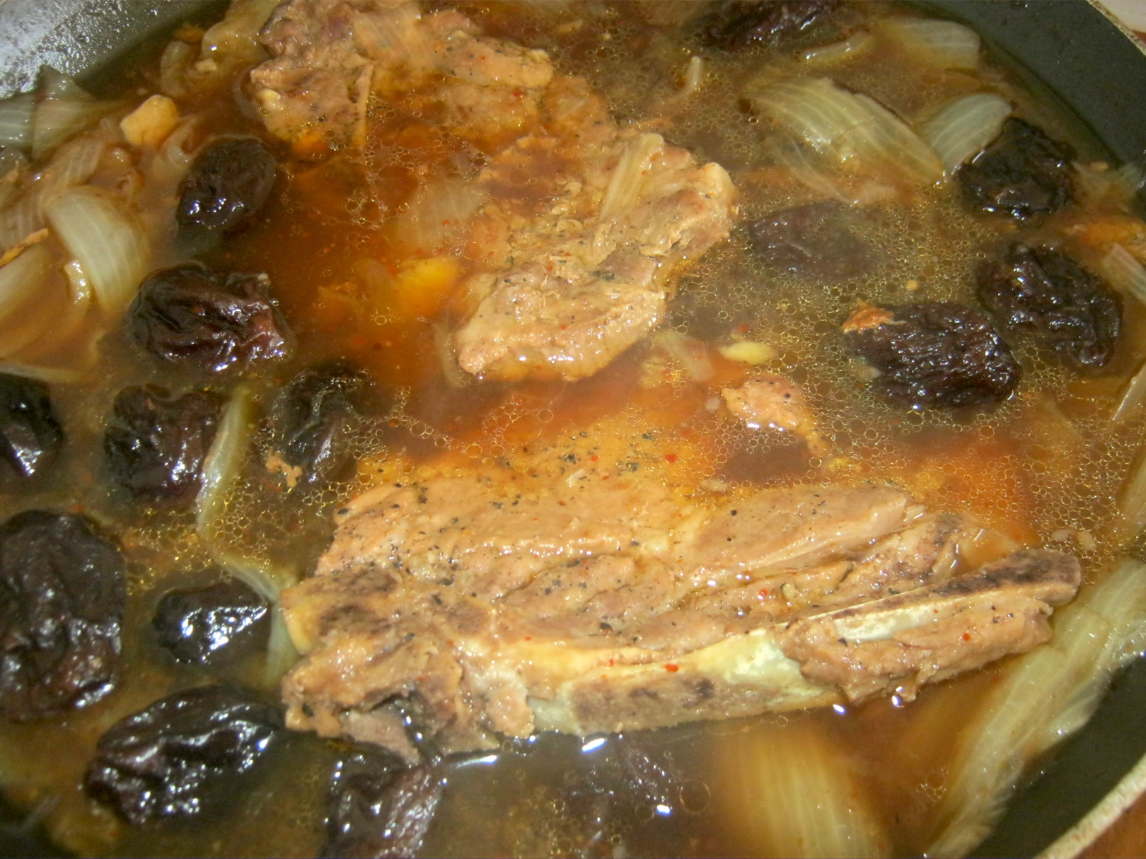 pork chops and whole prunes in pan