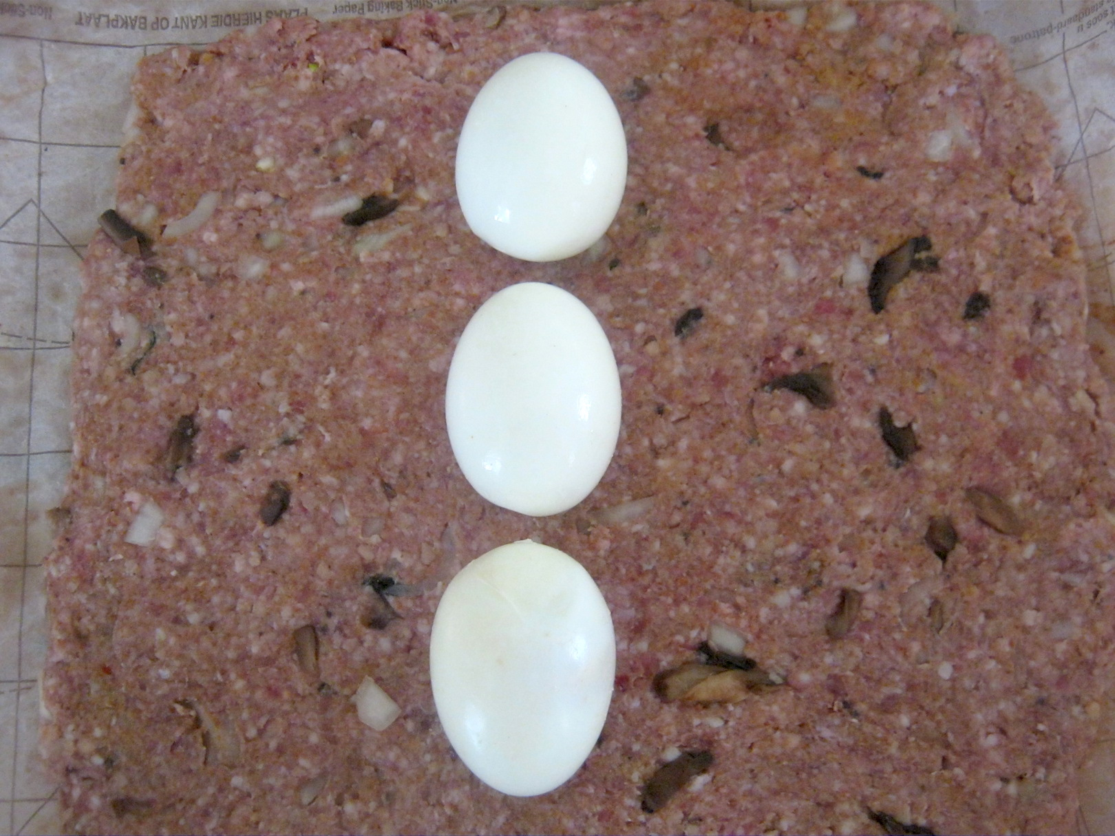 raw meatloaf dough rolled out with eggs on top