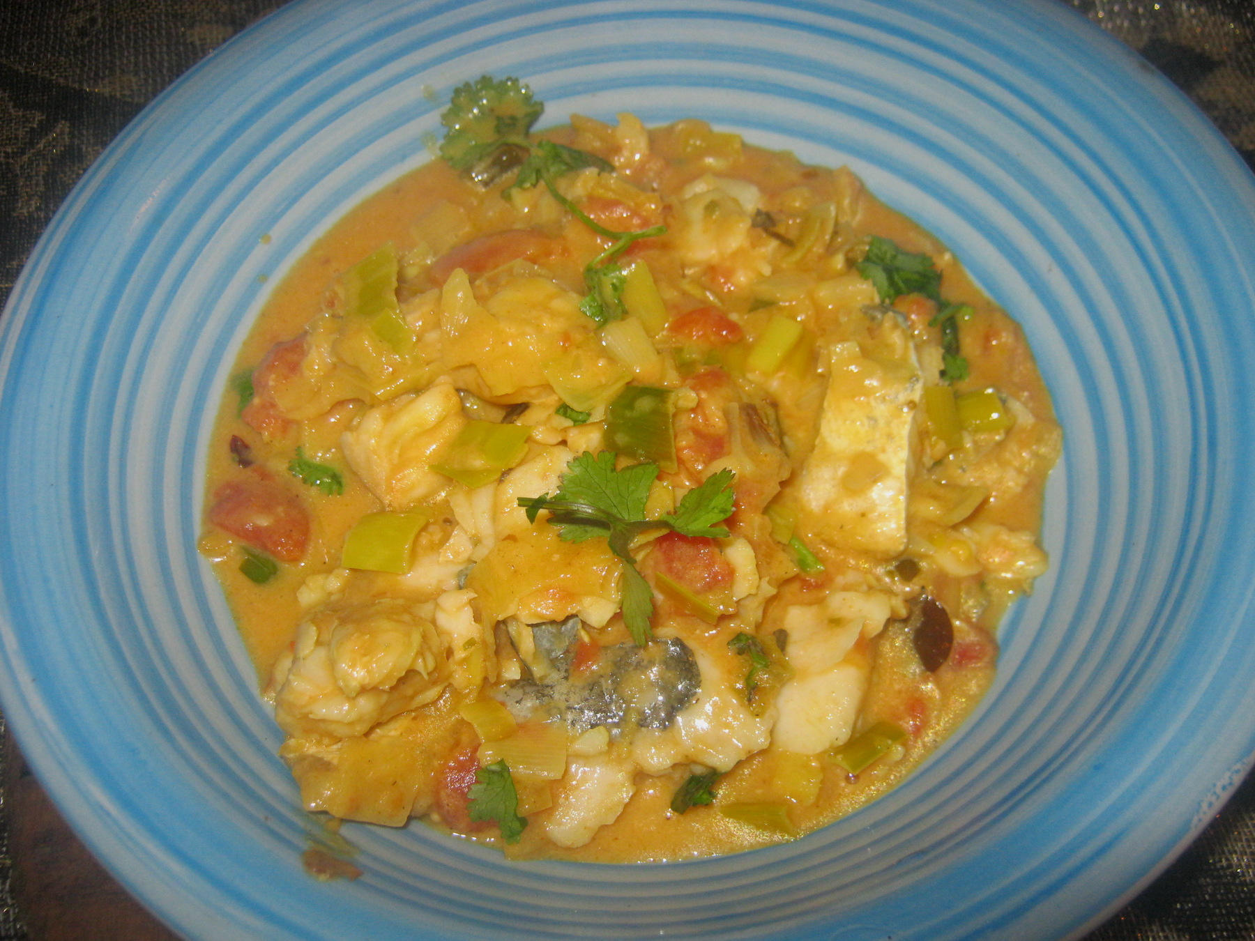 Hake curry in a blue bowl