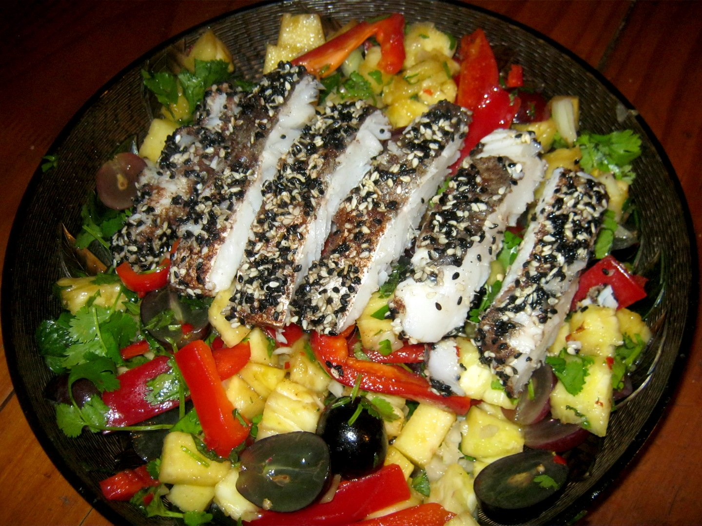 Hake in Cinnamon Sesame Crust on a bed of pineapple grape chili salad ion a serving tray