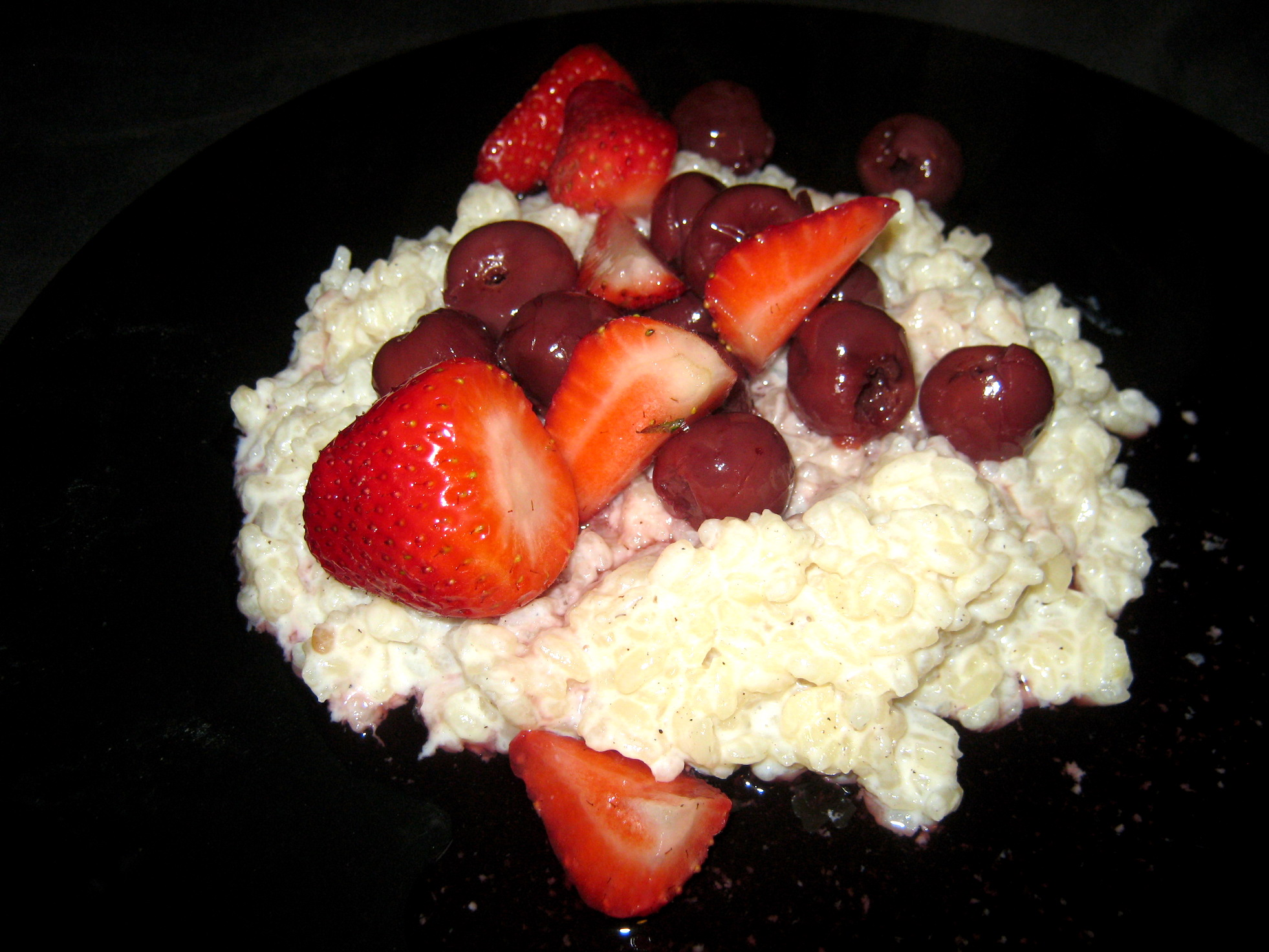Oma's Milchreis - Rice Pudding with cherries and strawberries on black plate