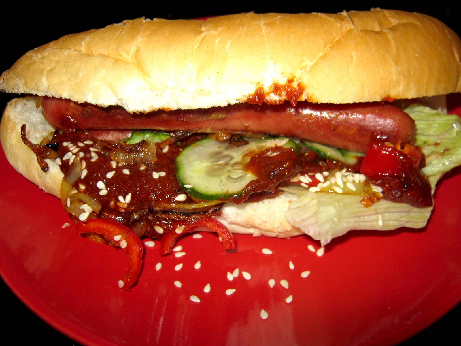 Quick hot dog with lettuce, cucumber, tomato, braised onions, jalapeno pepper, sesame seeds and a German style sweet and spicy curry sauce