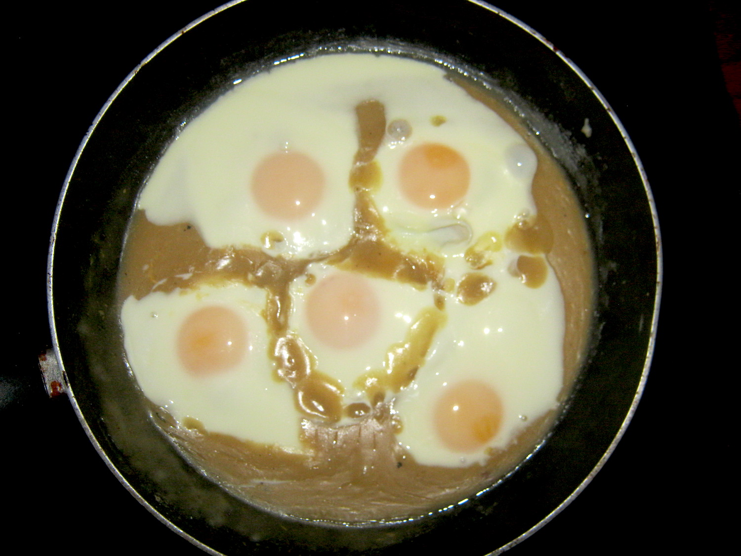 Poached eggs in a pan with sweet and sour mustard sauce