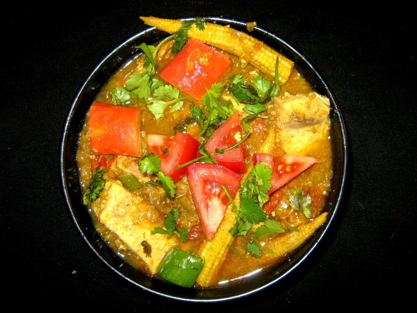 Swordfish curry with mixed seafood and baby corn in white bowl