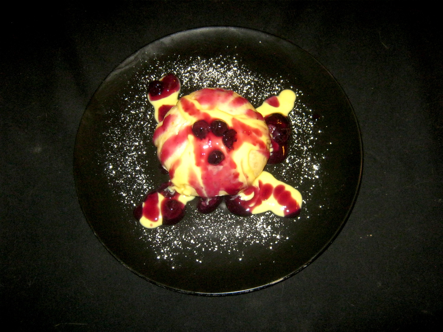 Yeast dumpling with blueberry sauce and custard on a black plate