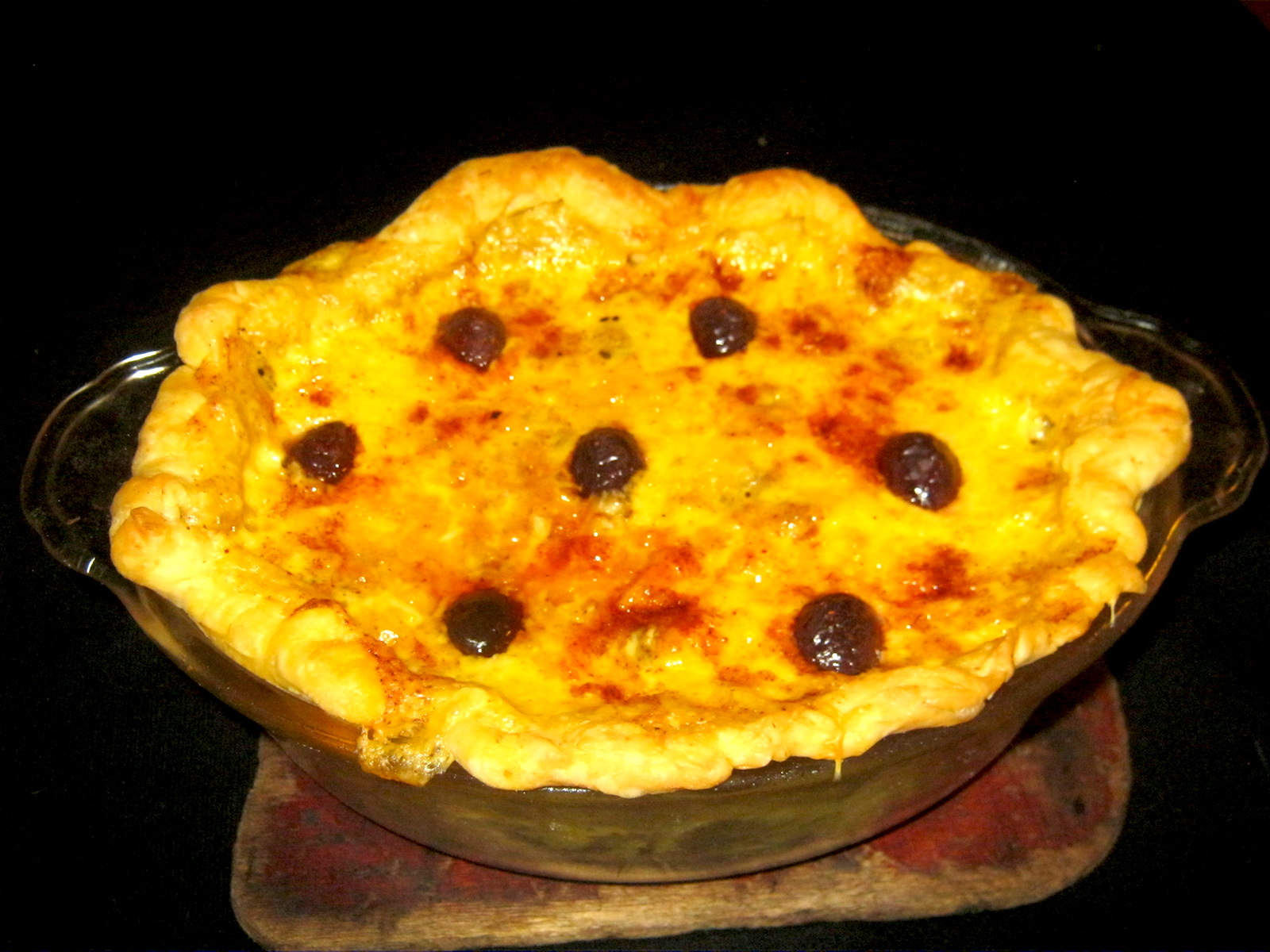 Baked chicken pot pie garnished with olives in casserole dish